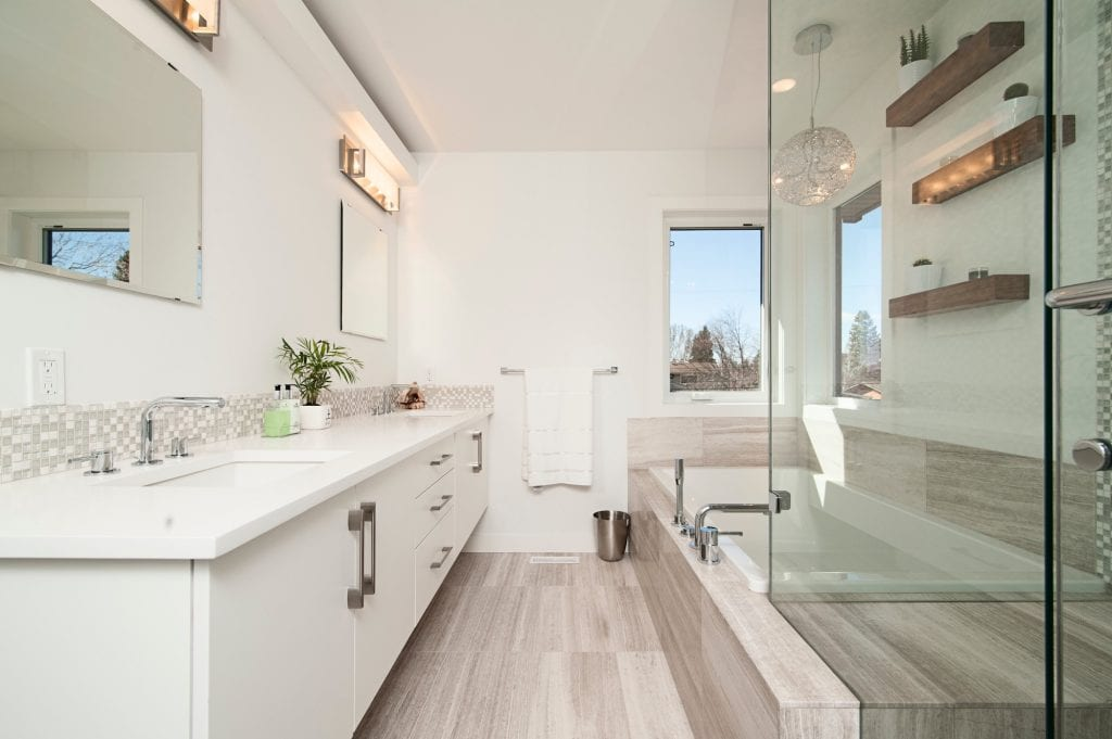 renovated bathroom with glass shower and soaking tub