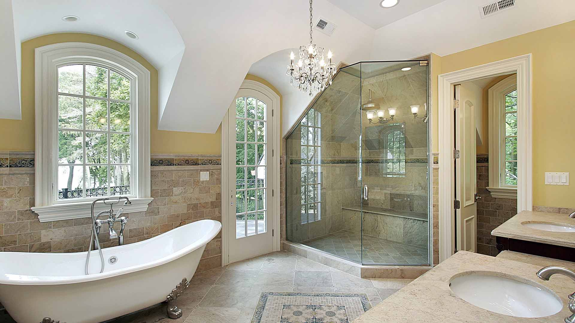 large master bath, design in floor tile, travertine floor tile, travertine wall tile, claw-foot tub, free standing tub filler, travertine counter tops, frameless shower glass, tile on bathroom walls, bathroom chandelier, shower with slope ceiling