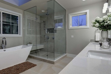 large greige master bath, free standing tub, freestanding tub faucet, skylight in master bath, frameless glass shower, recessed shower caddy, shower head from ceiling, shower bench, quartz countertops, chrome fixtures, large floor tile, double sink vanity