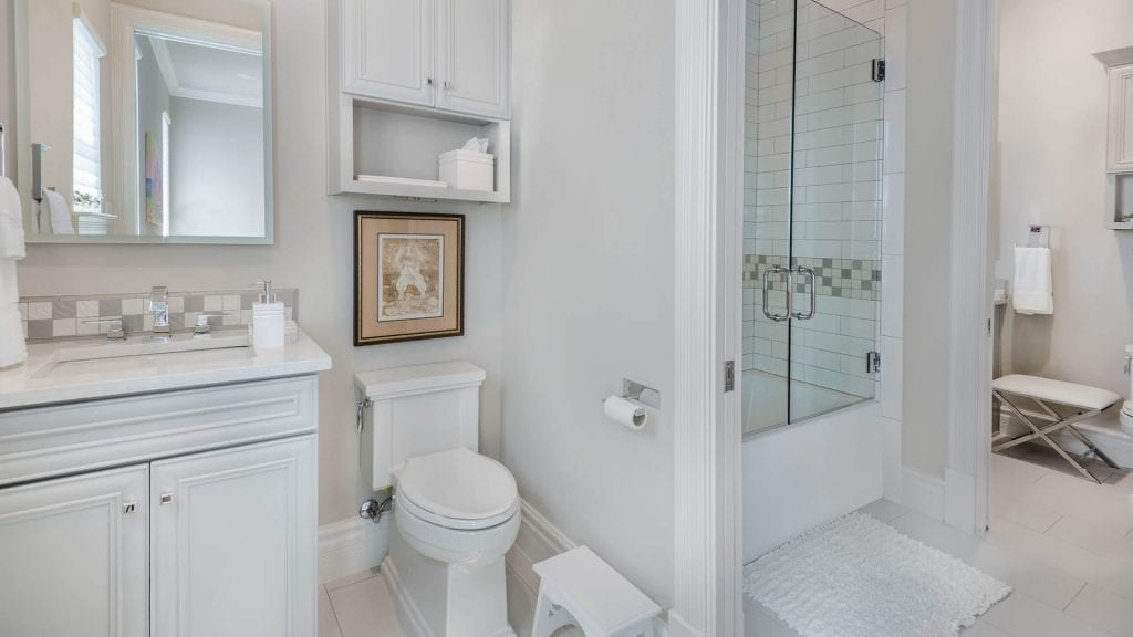 white vanity, white quartz vanity, Jack and Jill bathroom, square tank toilet, over toilet cabinet, white subway tile shower, frameless shower glass doors on tub, white subway tile with gray grout, framed vanity mirror, decorative tile vanity backsplash