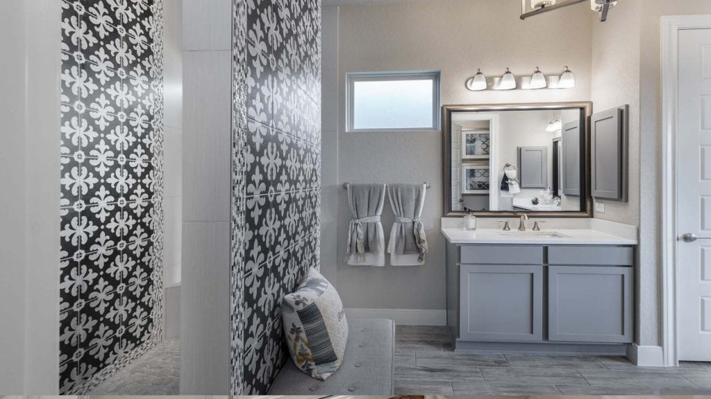 gray vanity cabinets, white quartz vanity top, framed vanity mirror, gray elongated tile floor, eclectic tile accent wall in bathroom, built-in bench seating in bath, ceiling mounted shower head, walk thru shower design, recessed medicine cabinet, chandelier in bathroom