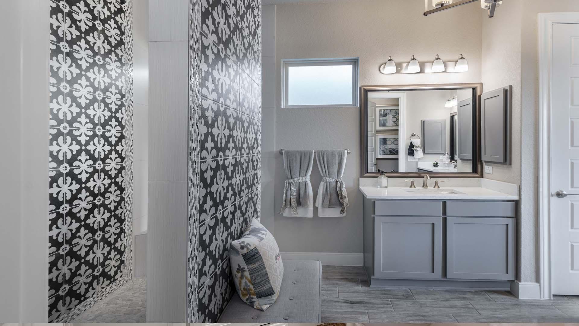 gray vanity cabinets, white quartz vanity top, framed vanity mirror, gray elongated tile floor, eclectic tile accent wall in bathroom, built-in bench seating in bath, ceiling mounted shower head, walk thru shower design, recessed medicine cabinet, chandelier in bathroom