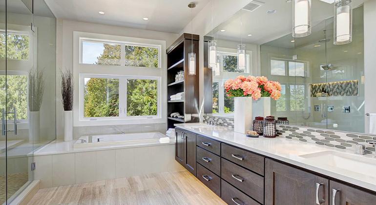 Shaker cabinets, brown cabinets, under mount sinks, large bathroom, vanity tile backsplash, tan floor, soffit over vanity, pendant light over vanity