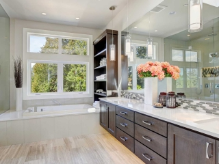 Shaker cabinets, brown cabinets, under mount sinks, large bathroom, vanity tile backsplash, tan floor, soffit over vanity, pendant light over vanity