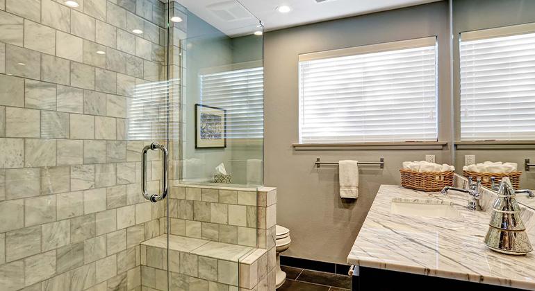 Stone shower tile, frameless shower glass, brick pattern tile