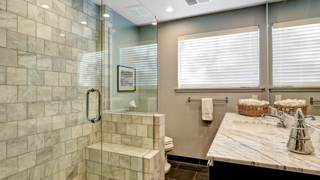 Stone shower tile, frameless shower glass, brick pattern tile