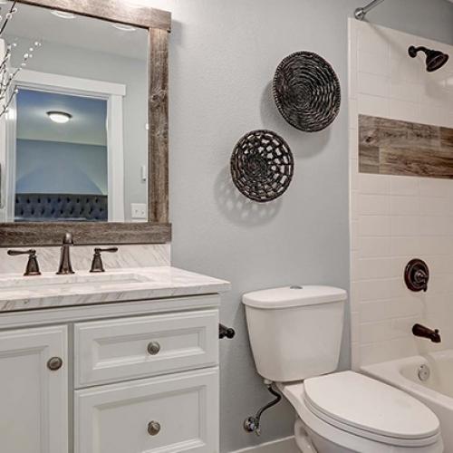 Hall bathroom, small bathroom, white vanity, light color vanity top, tile deco strip, white bathtub surround tile, framed mirror, white tub