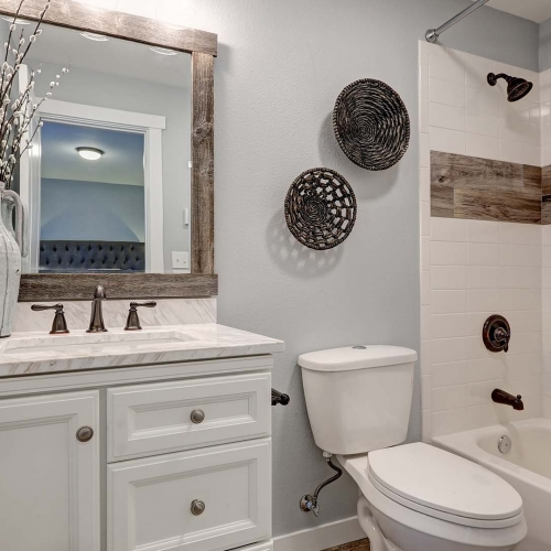 Hall bathroom, small bathroom, white vanity, light color vanity top, tile deco strip, white bathtub surround tile, framed mirror, white tub