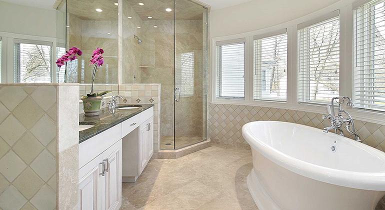 Travertine flooring, diagonal tile pattern, pedestal tub, floor to ceiling frameless shower glass, white cabinets, large master bath