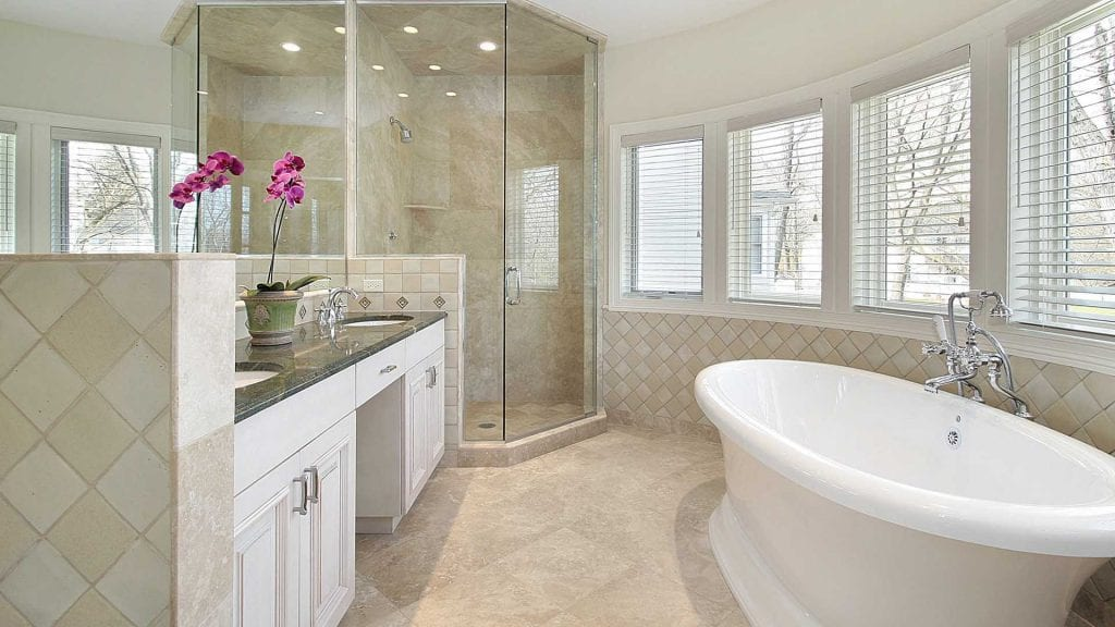 Travertine flooring, diagonal tile pattern, pedestal tub, floor to ceiling frameless shower glass, white cabinets, large master bath