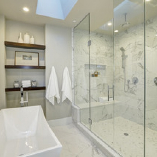 White Carrera marble tile shower, frameless glass shower, ceiling mounted shower head, hand held shower, recessed caddy, mosaic tile in shower caddy, shower bench, quartz shower bench, free standing tub, free standing tub faucet, floating wood shelves, chrome bath fixture