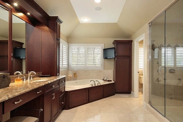 Large shower, frameless shower glass, knee drawer space, marble countertop, marble bathroom flooring, corner drop in tub, deck mounted faucet, wood panels on tub skirt, tall utility cabinet, vanity soffit with small can lights, wood framed vanity mirrors, dark wood cabinets, full overlay cabinets