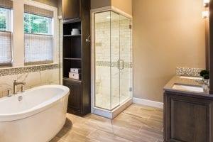 detailed tile shower, elongated hardwood floor tile, gray quartz countertop, gray raised panel cabinet doors, frameless glass shower, free standing tub, bathroom deco strip, bathroom cabinet with open shelving