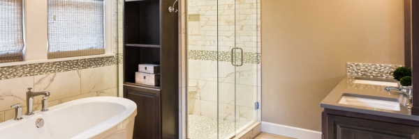 detailed tile shower, elongated hardwood floor tile, gray quartz countertop, gray raised panel cabinet doors, frameless glass shower, free standing tub, bathroom deco strip, bathroom cabinet with open shelving