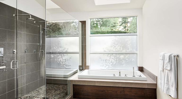 gray tile shower, two shower heads in master shower, mosaic shower floor, wood faced tub deck, frameless glass shower, hardwood tile floor, bright master bathroom, large shower in master bathroom