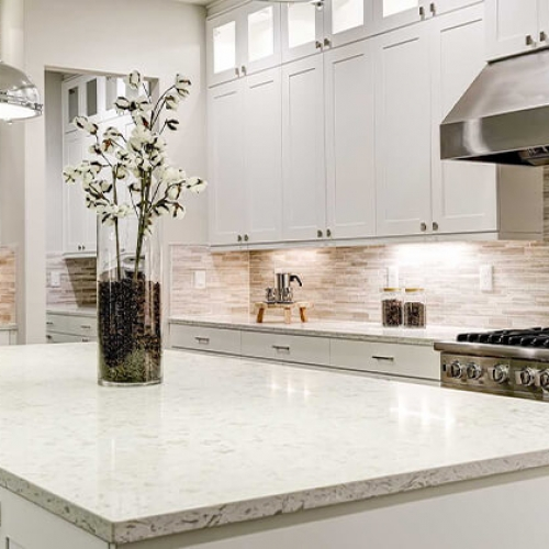 stainless vent hood, stainless pendant lights, stacked cabinets, white cabinets, stainless steel refrigerator, stone tile backsplash white cabinets