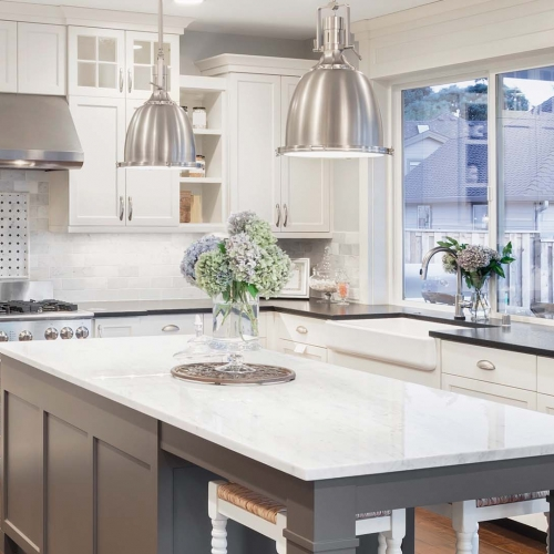 Gray island, seating at end of island, white cabinets, white countertops, stainless pendant lights, stacked cabinets, white cabinets, stainless steel appliances, stainless steel hood