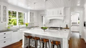 White ceiling, wood ceiling, island seating, white cabinets, wood cabinet hood, glass cabinet doors, hardwood floor, pendant lights