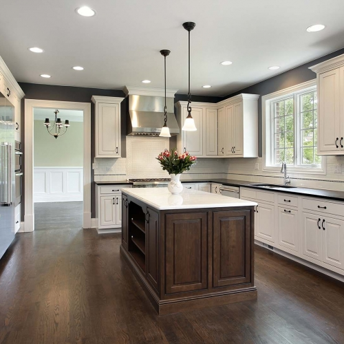 Dark Wood floors, brown island, white cabinets, raised panel cabinet doors, white island top, island with bookshelves, subway tile backsplash, Black countertops, Stainless vent hood