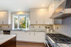 "Stainless steel hood, shaker cabinet doors, riser board, 36"" wall cabinets, white cabinets, hardwood floor, stainless slide in range"