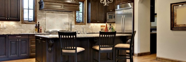 Hardwood Floor, dark brown cabinets, mocha cabinets, arch doorway, wood cabinet hood, raised panel doors stone backsplash