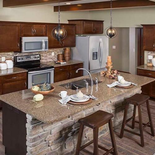 standard overlay cabinets, shaker, stack stone island, LVP flooring, brown cabinets, brown quartz, linear backsplash, sink in island, round pendent lights, exposed beams