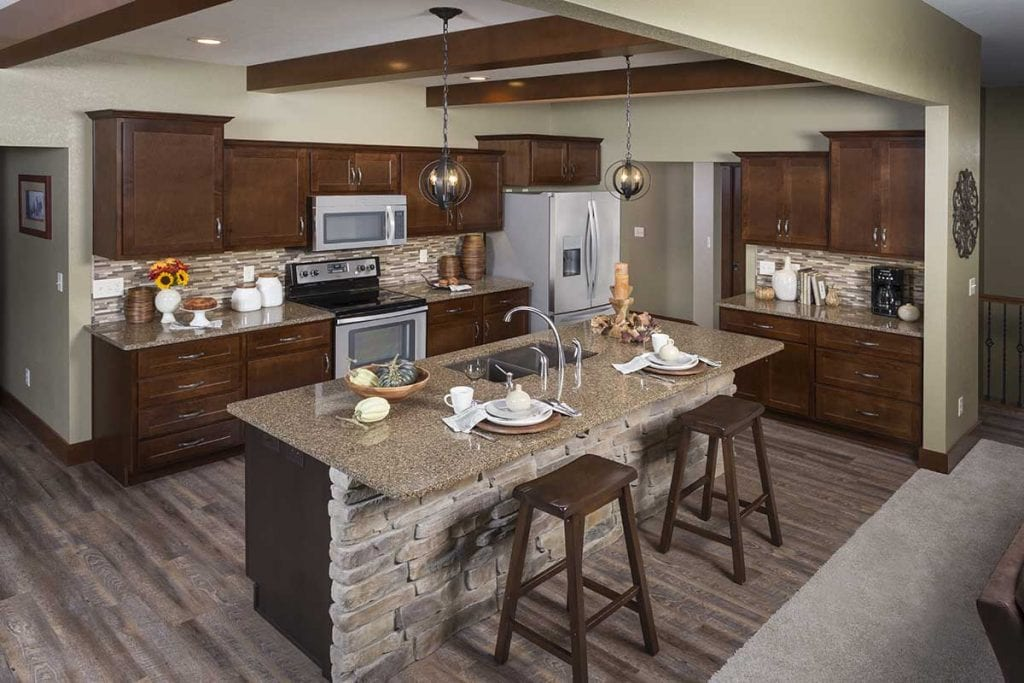 standard overlay cabinets, shaker, stack stone island, LVP flooring, brown cabinets, brown quartz, linear backsplash, sink in island, round pendent lights, exposed beams