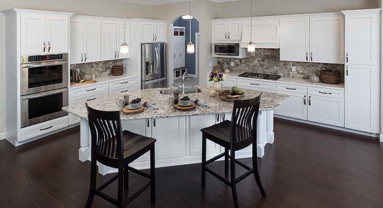 full overlay cabinets, white kitchen cabinets, island with rear storage, decorative island legs, LVP flooring, natural stone tile backsplash, island seating, pot filler, wood vent hood