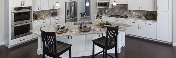 full overlay cabinets, white kitchen cabinets, island with rear storage, decorative island legs, LVP flooring, natural stone tile backsplash, island seating, pot filler, wood vent hood