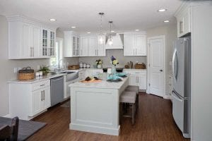 full overlay cabinets, white kitchen cabinets, island with decorative end panel, LVP flooring, island seating, quartz counter tops, wood vent hood, glass cabinet doors, farm sink