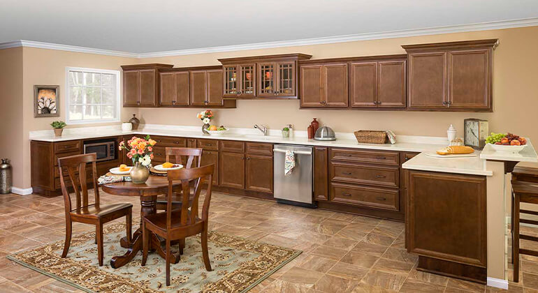 standard overlay cabinet, undercounter microwave, stainless appliances, medium brown stained cabinets, white quartz countertops, glass cabinet doors