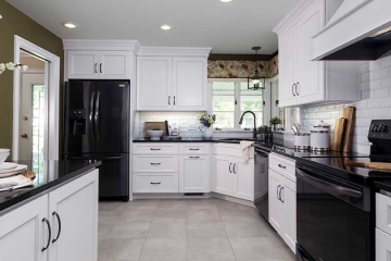 black appliances, subway tile backsplash with beveled edge, wood vent hood, black granite countertops