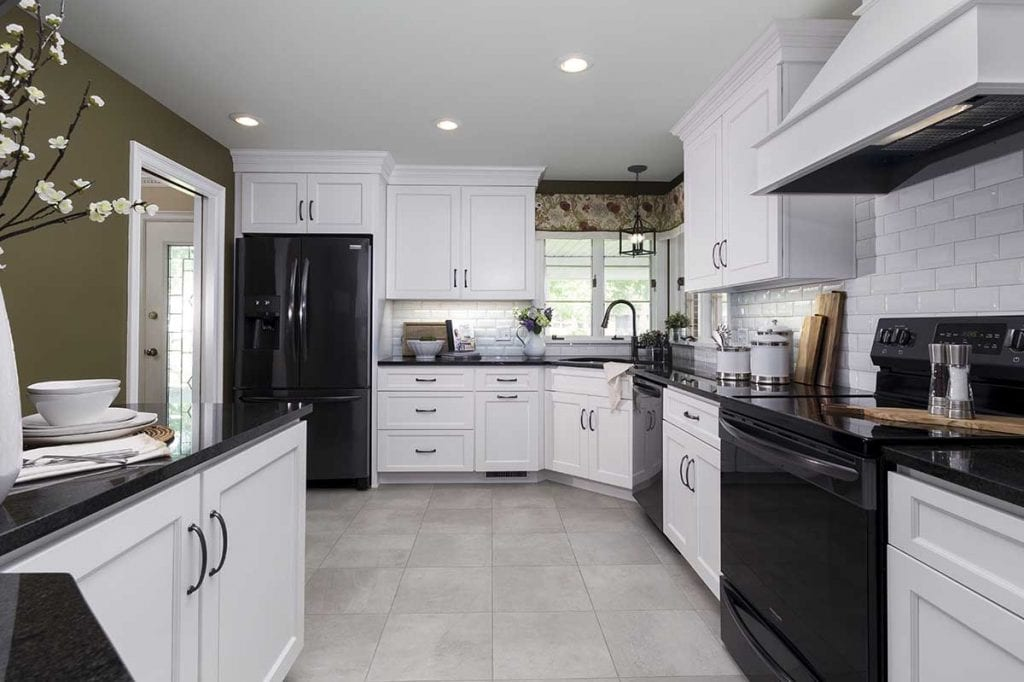 black appliances, subway tile backsplash with beveled edge, wood vent hood, black granite countertops