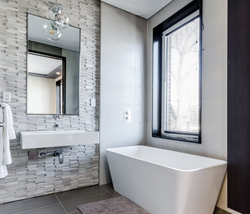 remodeled bathroom with beautiful tiled wall and gorgeous tub
