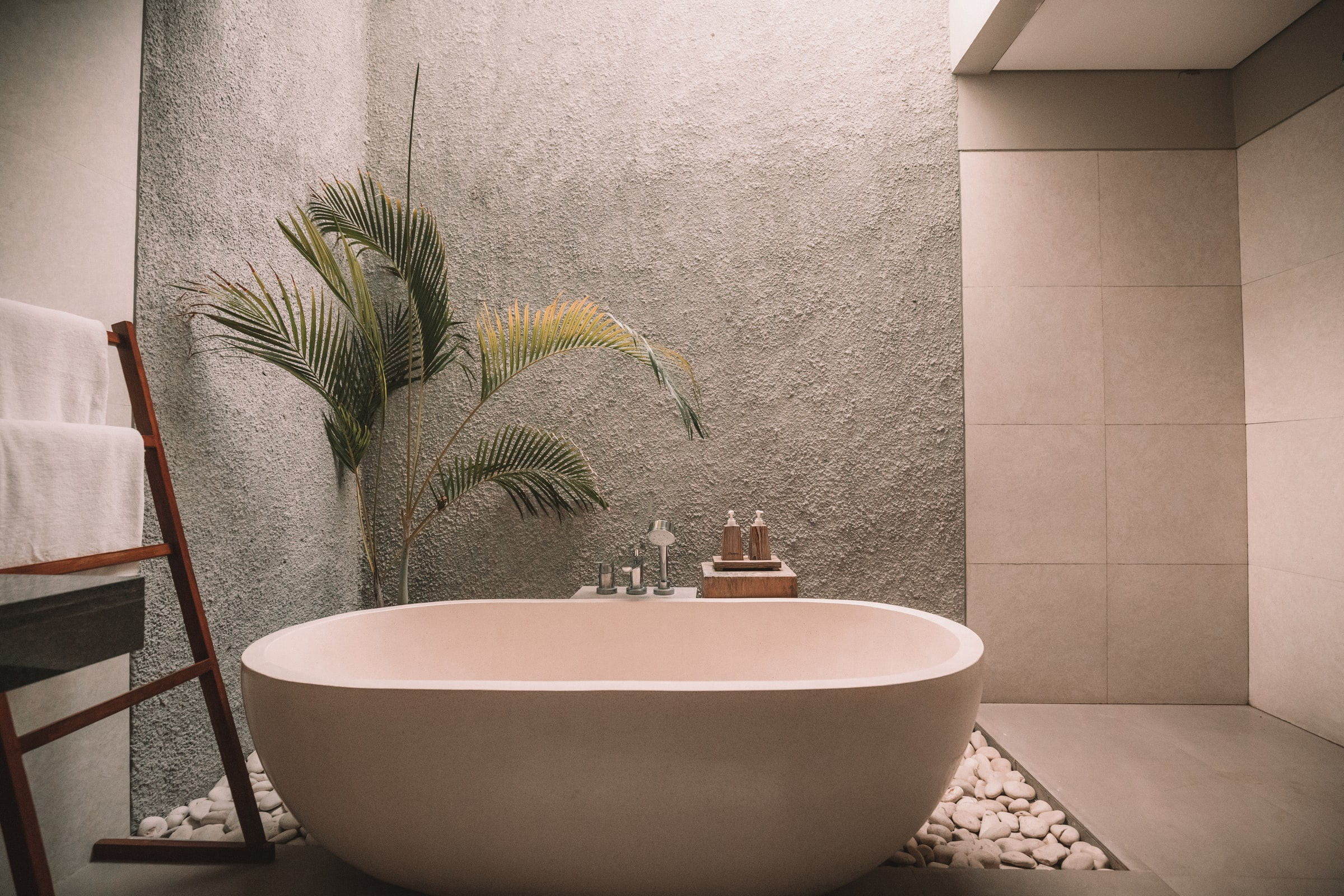 A bathroom remodel with a white bathtub and a plant and planter rocks behind the tub.